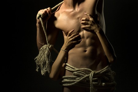 undressed: Young undressed handsome man with sexy strong muscular body with long durable rope and female hands standing on studio black background, horizontal picture Stock Photo