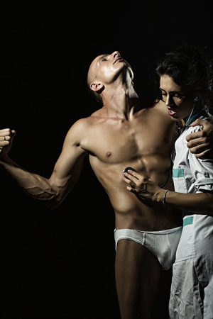 Sexy young couple of undressed man in pants with strong muscular beautiful body and pretty brunette nurse in white smock with stethoscope standing on black studio background, vertical picture Stock Photo