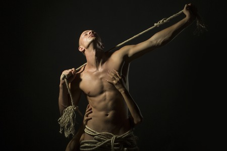 undressed: Young undressed handsome man with sexual strong muscular body with long durable rope and female hands standing on studio black background, horizontal picture