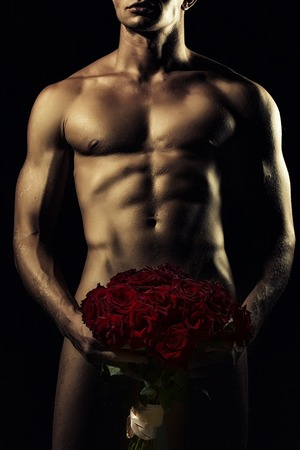 Young sexy undressed man with beautiful strong muscular body holding big fresh red rose flowers bouquet on genitals standing on black background, vertical picture Stock Photo