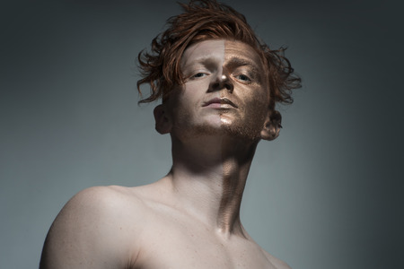 bronzy: One young fashionable painted man model with bronzy bodyart on one half of face and stylish red hairdo looking forward standing in studio on grey background, horizontal picture