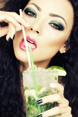 Closeup of sensual young brunette woman with curly hair and bright makeup drinking alcoholic mojito cocktail from mint soda light rum ice cubes and lime with straw, vertical picture Stock Photo