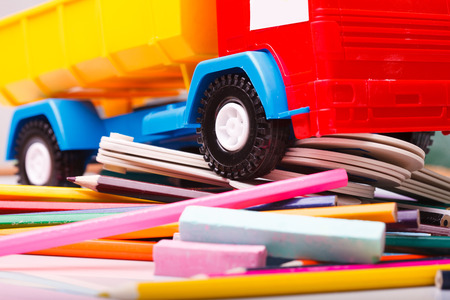 purple car: Colorful pencils of red yellow orange violet purple pink green blue chalk fan english alphabet and truck car toy lying on white school desk background, horizontal photo