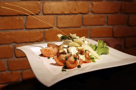 crist: Tasty light fresh salad consisiting of cutted tomatoes with parmesane cheese sliced green onion crisp croutons decorated with parsley and lettuce on square white plate, horizontal picture
