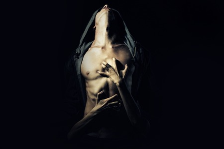 niño sin camisa: Joven pareja de chico con un fuerte cuerpo musculoso sexy en la chaqueta de cuero con capucha mirando hacia arriba y niña abrazando con las manos de pie en el estudio de fondo negro, cuadro horizontal Foto de archivo