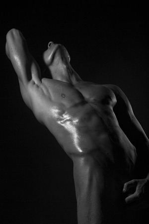 One young naked guy with sexy strong muscular beautiful wet body holding one hand on genitals and other raised standing on black studio background, vertical picture