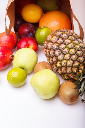 Fresh tropical fruits of pineapple orange juicy grapefruit yellow lemon ripe nectarine purple plum red pomegranate kiwi lime and green apple and paper pack on white background, vertical picture 版權商用圖片
