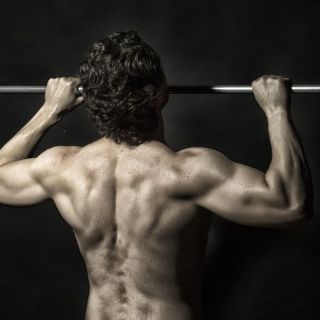 strong chin: Back view of one young muscular sexy attractive athletic strong guy with brunette curly hair doing chin-ups on metal bar with bare beautiful wet body on black studio background, square picture Stock Photo