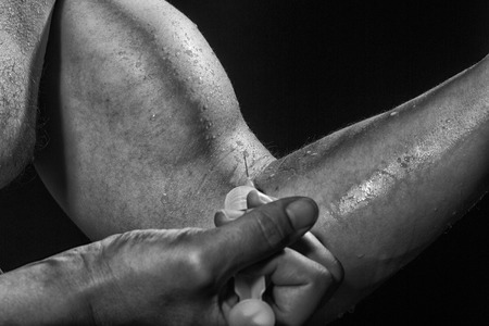 musculation: Closeup of muscular male wet arm of young sportsman with big biceps and syringe with thin needle as symbol of medicine anabolocs or drugs making injection black and white, horizontal picture