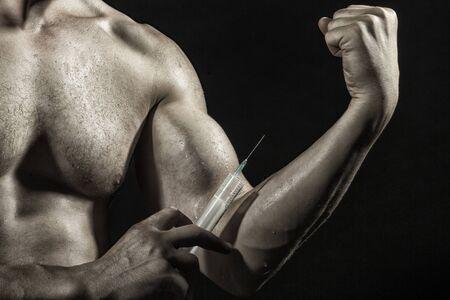 nackte brust: Nackte Brust und muskul�sen m�nnlichen nassen Arm des kleinen Jungen mit gro�en Bizeps und Spritze mit d�nner needl als Symbol der Medizin anabolocs oder Drogen machen Injektion auf schwarz Studio Hintergrund, horizontale Abbildung