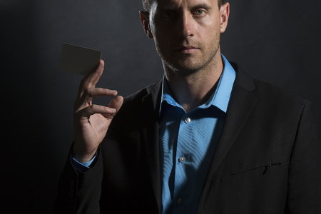 young unshaven: Portrait of one handsome sexual unshaven young man in jacket and blue shirt holding white business card in hand looking forward standing on black studio background copyspace, horizontal picture