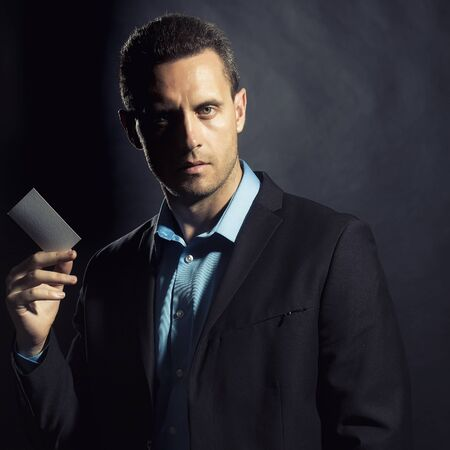 young unshaven: Portrait of one handsome sexual unshaven young business man in jacket and blue shirt holding white calling card in hand looking forward standing on black studio background copyspace, square picture Stock Photo