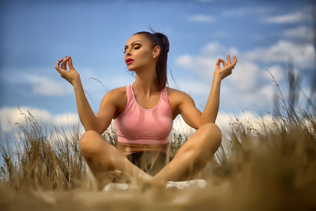 freedom leisure activity: One sexual young brunette woman with straight beautiful body in sportswear sitting on grall relaxing and making meditation while morning running outdoor on blue sky background, horizontal picture