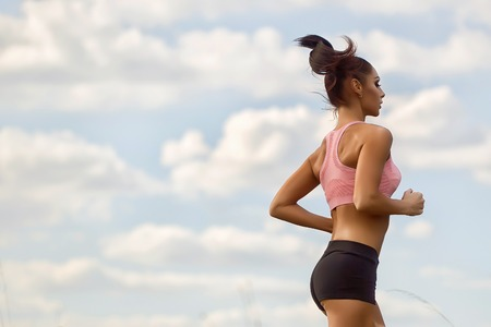 freedom leisure activity: One sexual slim young brunette active woman with straight beautiful body in sportswear on morning running outdoor side view on cloud blue sky background copyspace, horizontal picture Stock Photo