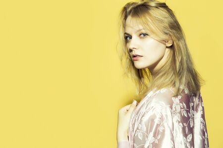 patterns and colors: One beautiful young sensual pensive woman with blond hair in satin pink dressing gown in soft flower pattern pastel colour standing on yellow studio background copyspace, horizontal picture Stock Photo