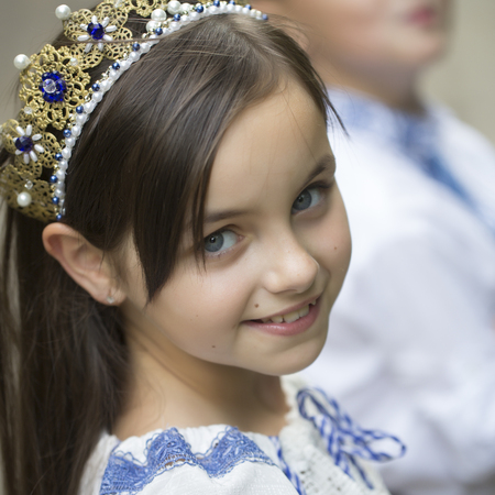 lon: Portrait of cute smiling princess girl with long brunette hair in traditional ukrainian embroidery white blue colors and beautiful diadem with diamonds in gold looking forward, square picture Stock Photo