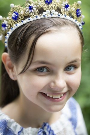 lon: Closeup of pretty smiling princess girl with long brunette hair in traditional ukrainian embroidery white blue colors and beautiful diadem with diamonds in gold outdoor, vertical picture Stock Photo