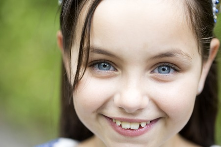 close up eyes: Portrait of beautiful little smiling girl with brunette hair and blue eyes in white blouse looking forward standing sunny day outdoor on natural background closeup, horizontal picture