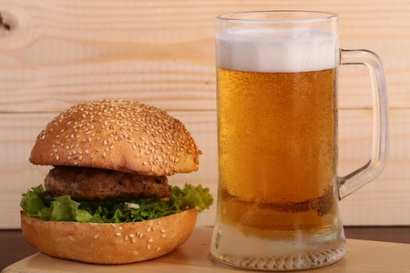 octoberfest: Big fresh tasty burger of green lettuce meat cutlet tomato and white bread bun with sesame seeds near and glass of light beer with froth on octoberfest holiday on wooden background, horizontal picture