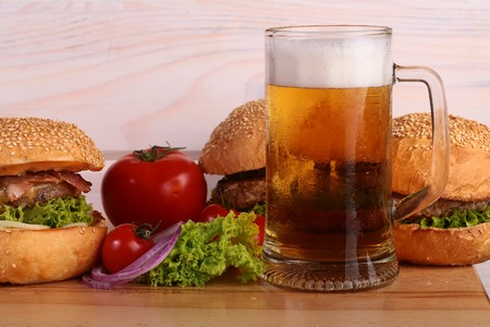 near beer: Few fresh tasty burgers of green lettuce meat cutlet tomato and white bun with sesame seeds near and glass of light beer with froth on octoberfest holiday on wooden background, horizontal picture Stock Photo