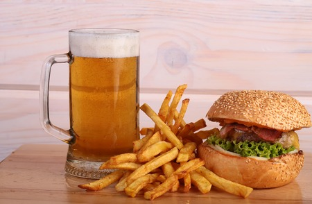 near beer: Big fresh tasty burger of green lettuce meat cutlet cheese tomato and white bread bun with sesame seeds near chips and glass of light beer on octoberfest holiday, horizontal picture