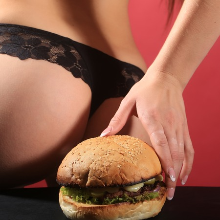 lace panties: One female sexy bottom of young woman in black lace panties holding big fresh tasty burger of green lettuce meat cutlet cheese and white bun with sesame seeds on red background, square picture