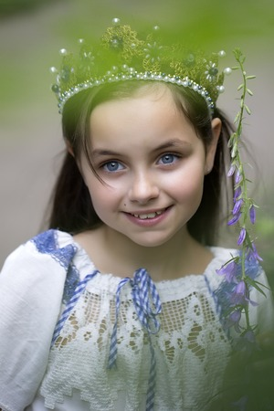 lon: Portrait of pretty smiling princess girl with long brunette hair in traditional ukrainian embroidery white blue colors and beautiful diadem with diamonds in gold outdoor, vertical picture