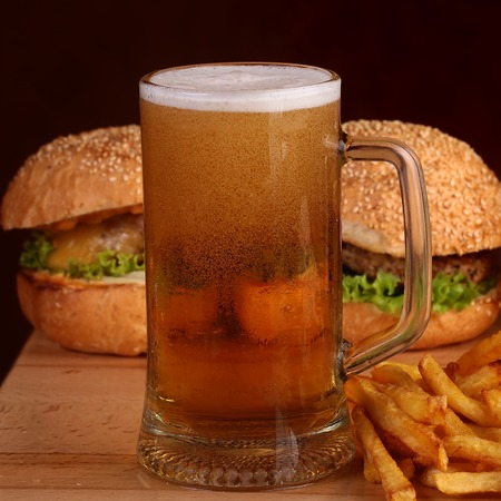 near beer: Two fresh tasty burgers of green lettuce meat cutlet cheese tomato and white bread bun with sesame seeds near chips and glass of light beer on octoberfest holiday, square picture