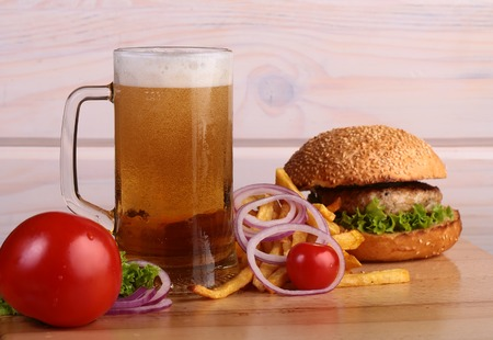 octoberfest: Big fresh tasty burger of green lettuce meat cutlet cheese tomato and white bread bun with sesame seeds near chips and glass of light beer on octoberfest holiday, horizontal picture