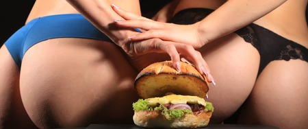 lace panties: Two female bottoms of young girls in blue and black lace panties holding one big fresh tasty burger of green lettuce meat cutlet cheese onion and white bread bun with sesame seeds, horizontal picture Stock Photo