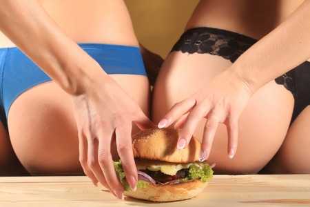 lace panties: Two female bottoms of young ladies in blue and black lace panties holding one big fresh tasty burger of green lettuce meat cutlet cheese onion and white bread bun with sesame seeds, horizontal picture Stock Photo