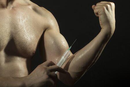 nackte brust: Nackte Brust und muskul�sen m�nnlichen nassen Arm des jungen Mannes mit gro�en Bizeps und Spritze mit d�nner needl als Symbol der Medizin anabolocs oder Drogen machen Injektion auf schwarz Studio Hintergrund, horizontale Abbildung Lizenzfreie Bilder