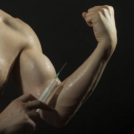 musculation: Closeup of muscular male wet arm of young athlete guy with big biceps and syringe with thin needl as symbol of medicine anabolocs or drugs making injection on black studio background, square picture Stock Photo
