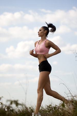 pretty brunette woman: Full length one pretty slim young brunette active woman with straight beautiful body in sportswear on morning running outdoor side view on cloud blue sky background, vertical picture Stock Photo