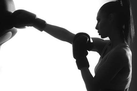Side view of one strong concentrated female boxer with ponytail in boxing gloves training punching standing in studio on white background black and white copyspace, horizontal picture
