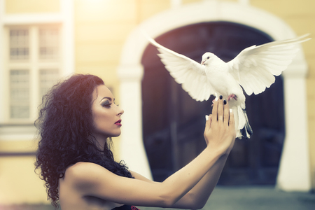 Charming beautiful delicate young woman with bright make-up with long curly brown hair in profile holding a white pigeon in her hands on blur building background outdoor, horizontal picture Stock Photo