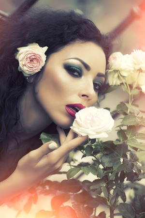 rosebush: Romantic pretty adorable woman with flower in curly brown long hair looking straight with professional makeup red lips emerald eyeshadow near white rosebush leaves outdoor closeup, vertical photo Stock Photo