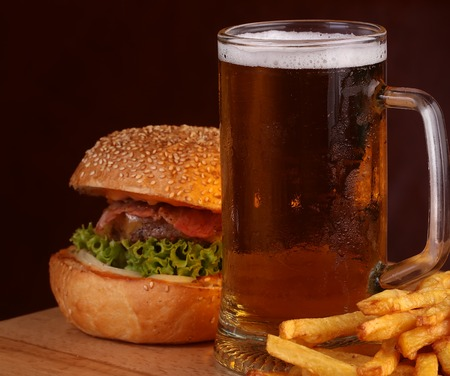 octoberfest: Big fresh tasty burger of green lettuce meat cutlet cheese tomato and white bread bun with sesame seeds near chips and glass of dark beer on octoberfest holiday, square picture