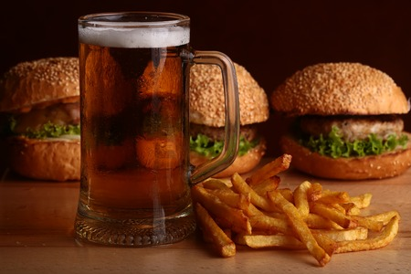 near beer: Three fresh tasty burgers of green lettuce meat cutlet cheese tomato and white bread bun with sesame seeds near chips and glass of dark beer on octoberfest holiday, horizontal picture Stock Photo