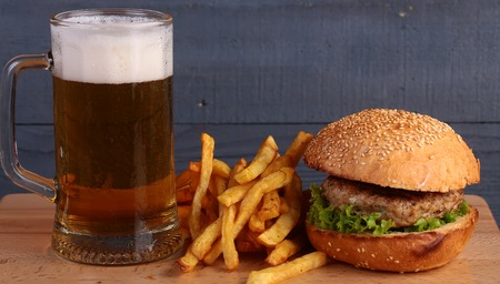 octoberfest: Big fresh tasty burger of green lettuce meat cutlet cheese tomato and white bread bun with sesame seeds near chips and glass of light beer on octoberfest holiday on grey background, horizontal picture Foto de archivo