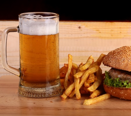 near beer: Big fresh tasty burger of green lettuce meat cutlet cheese tomato and white bread bun with sesame seeds near chips and glass of light beer on octoberfest holiday on wooden table, square picture Stock Photo