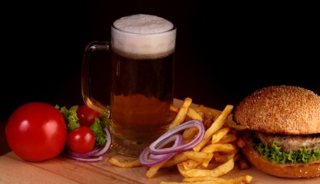 dark beer: Big fresh tasty burger of green lettuce meat cutlet cheese tomato and white bread bun with sesame seeds near chips and glass of dark beer on octoberfest holiday on black background, horizontal picture Stock Photo