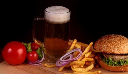 octoberfest: Gran sabrosa hamburguesa fresca de lechuga tomate verde carne chuleta y queso bollo de pan blanco con semillas de sésamo cerca de patatas fritas y vaso de cerveza oscura en vacaciones octoberfest sobre fondo negro, cuadro horizontal