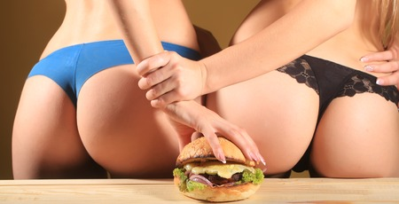 Two female bums of young weman in blue and black lace panties holding one big fresh tasty burger of green lettuce meat cutlet cheese onion and white bread bun with sesame seeds, horizontal picture