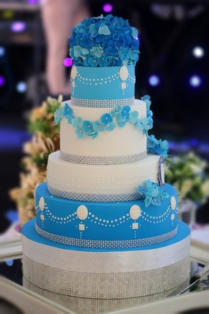 One big beautiful tasty many-tier decorated wedding cake white and blue colours with flower garlad and hydrangea bouquet on top, vertical picture Standard-Bild
