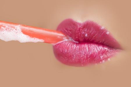 boca cerrada: Sexy completa magn�fica mujer seductora cerr� la boca de la mujer joven con los labios rosados ??potable c�ctel trav�s de la paja roja close-up, imagen horizontal Foto de archivo