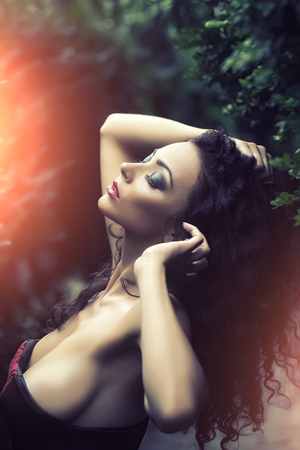 Portrait of awesome seductive glamour young big breasted woman with bright fashion makeup in dress with bare shoulders touching her curly hair profile on blur background outdoor, vertical picture