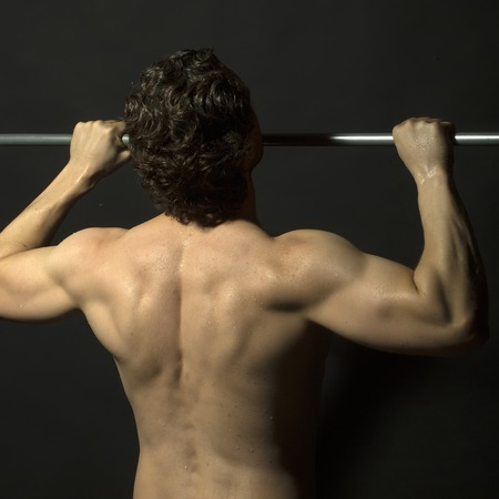 strong chin: Back view of one young muscular sexy attractive athletic strong male with brunette curly hair doing chin-ups on metal bar with bare beautiful wet body on black studio background, square picture Stock Photo