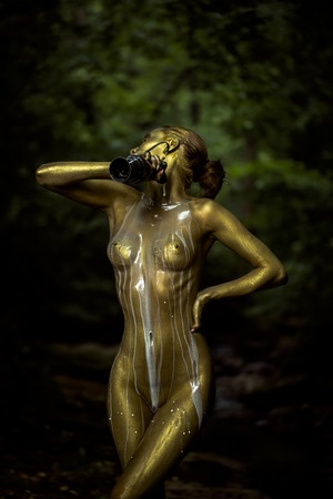 Girl with golden bodyart pouring white milk from jug on young sensual undressed female body standing near big stone with moss with bare chest belly pubis on natural background, vertical picture