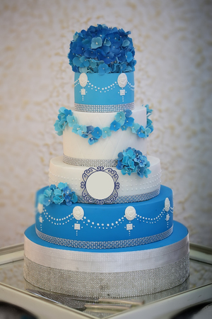 One large beautiful delicious many-tier decorated wedding cake white and blue colours with flower garlad and hydrangea bouquet on top, vertical picture